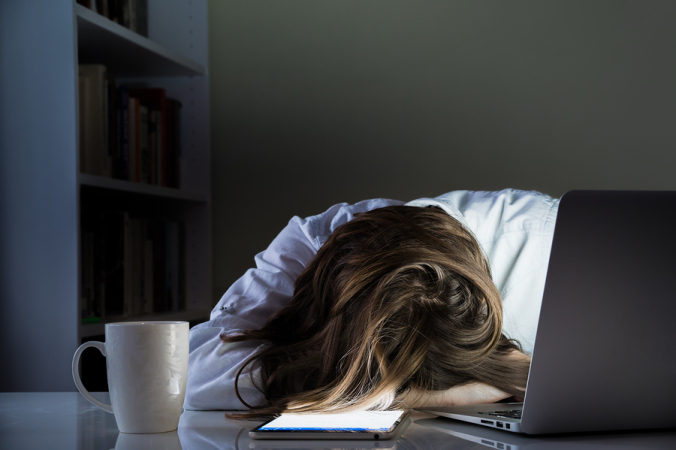 Exhausted female writer with head down on desk, laptop open, tablet nearby
